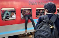 A migrant worker tries to board an overcrowded passenger train from an emergency window, after government imposed restrictions on public gatherings in attempts to prevent spread of coronavirus disease (COVID-19), in Mumbai, India, March 21, 2020. REUTERS/Prashant Waydande TPX IMAGES OF THE DAY