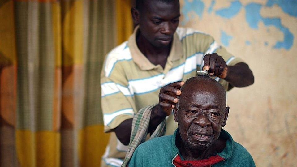 A man having his head shaved at a barbers in Ghana