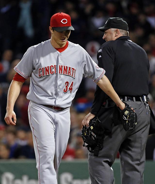 Cincinnati Reds starting pitcher Homer Bailey (34) gives home plate umpire Bill Welke a friendly pat after they chatted at the end of the sixth inning of a baseball game against the Boston Red Sox at Fenway Park in Boston, Tuesday, May 6, 2014. (AP Photo/Elise Amendola)