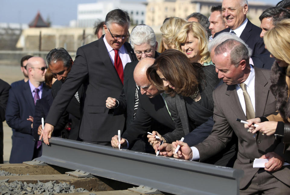 FILE - In this June. 18, 2015 file photo, Gov. Jerry Brown, center, and his wife, Anne Gust Brown, fourth from right, sign a portion of a rail at the California High-Speed Rail Authority in Fresno, Calif. Lawmakers and the Newsom administration are still trying to reach agreement on whether to give the project $4.2 billion that's left in the bond fund voters approved for high-speed rail in 2008. Rail officials say the need it to continue construction beyond next summer, but some state lawmakers want more oversight of the project before releasing it. (AP Photo/Gary Kazanjian, File)
