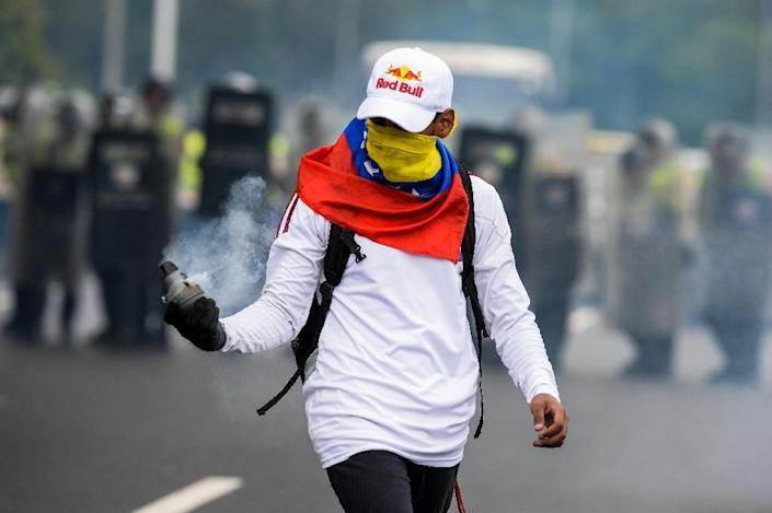An anti-Maduro protester holds a tear gas cannister during a demonstration in Caracas on May 11, 2016 (AFP Photo/Federico Parra)