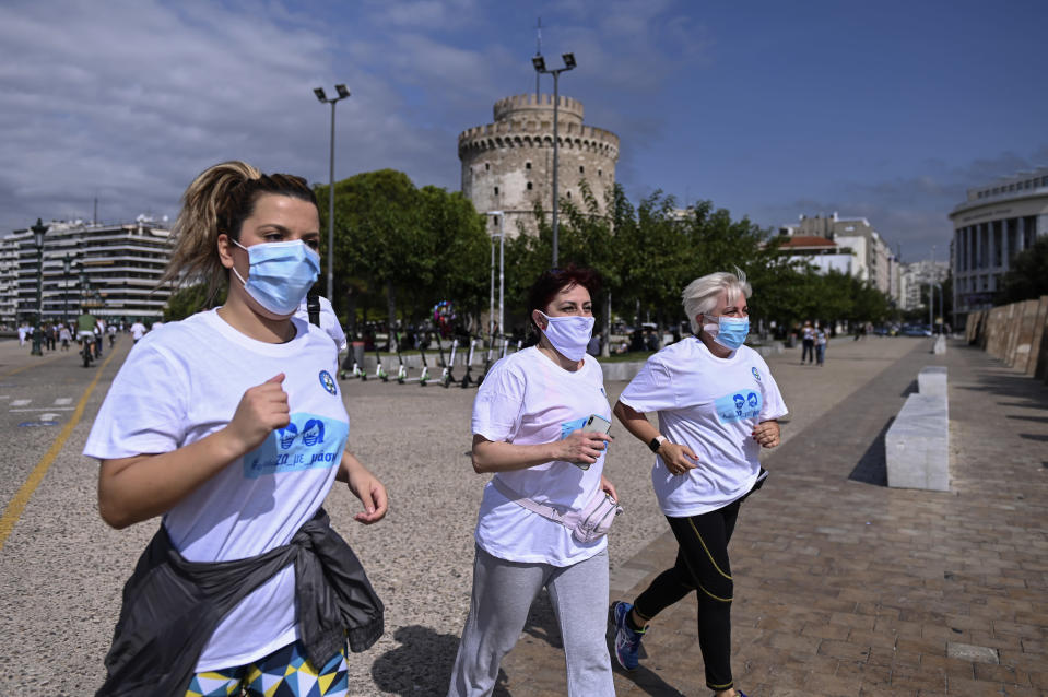 People participate in an event, organized by the local medical association, to support the use of protective masks, in the northern city of Thessaloniki, Greece, Saturday, Oct. 3, 2020. Lung doctors staged a public demonstration of the benefits of face masks by fast-walking a distance of 2 kilometers (1.25 miles) through the city center aiming to debunk a widely-circulated rumor by anti-mask conspiracy theorists that wearing one left people short of breath. (AP Photo/Giannis Papanikos)