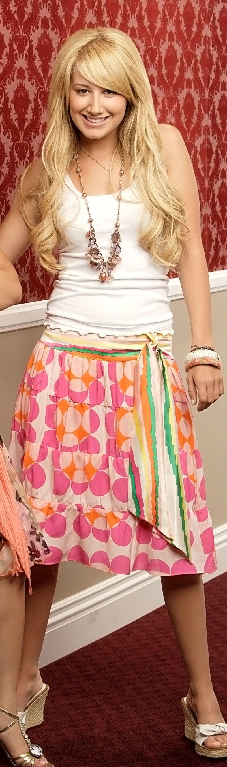 Maddie with a long past-the-knees large polka dot skirt with a sash at the waist with a tank top and long necklace with wedges
