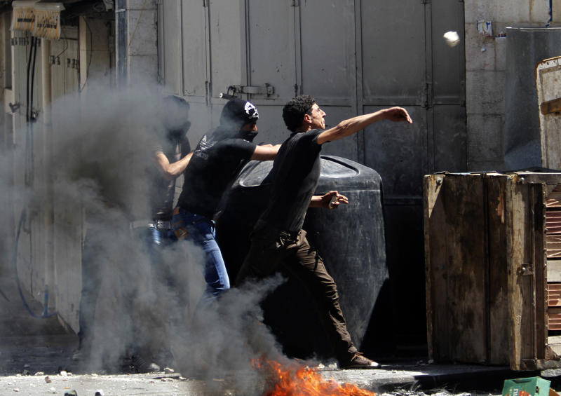 Palestinians throw stones at Israeli soldiers after the death of  Maysara Abu Hamdiyeh in Israeli jail in the West Bank city of Hebron, Tuesday, April 2, 2013. Abu Hamdiyeh, 64, who was serving a life sentence for his role in a foiled attempt to bomb a busy cafe in Jerusalem in 2002, died Tuesday of cancer in an Israeli jail. (AP Photo/Nasser Shiyoukhi)