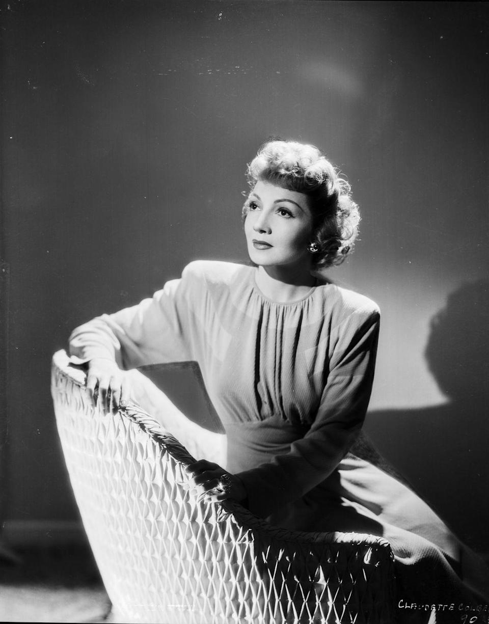 <p>Claudette Colbert sits for a portrait at Selznick Productions wearing a cinched dress with pronounced shoulders. </p>