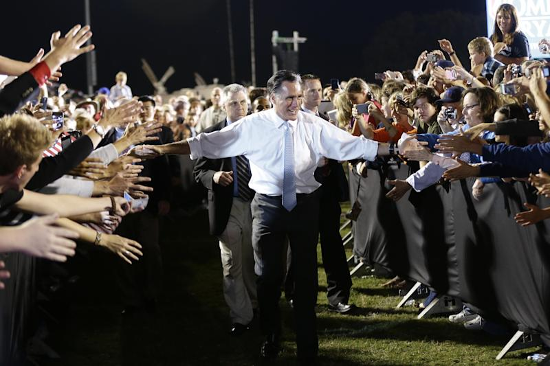 Republican presidential candidate and former Massachusetts Gov. Mitt Romney reaches out to supporters as he campaigns on the football field at Land O'Lakes High School in Land O'Lakes, Fla., Saturday, Oct. 27, 2012 after the motorcade was stopped. (AP Photo/Charles Dharapak)