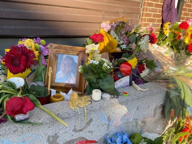 Flowers and candles surround a photo of Carl Reinboth at a makeshift memorial on Somerset Street W. on Sunday. The 64-year-old outreach worker at the Somerset West Community Health Centre was fatally stabbed nearby two days earlier. (Ryan Patrick Jones/CBC - image credit)