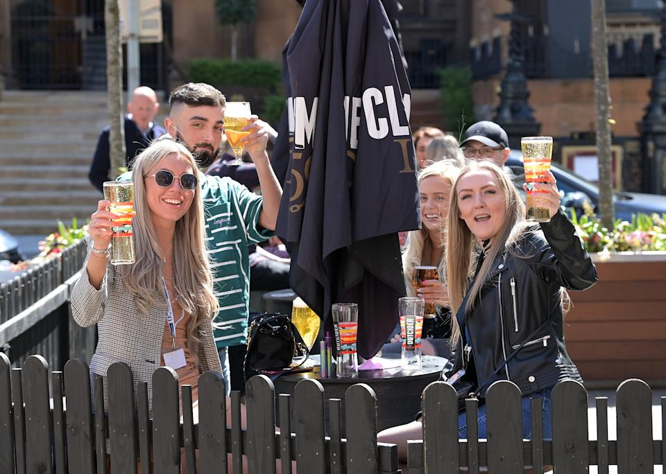 People raise their glasses as pubs with outdoor facilities reopen on 30 April in Belfast, Northern Ireland. Photo: Charles McQuillan/Getty Images