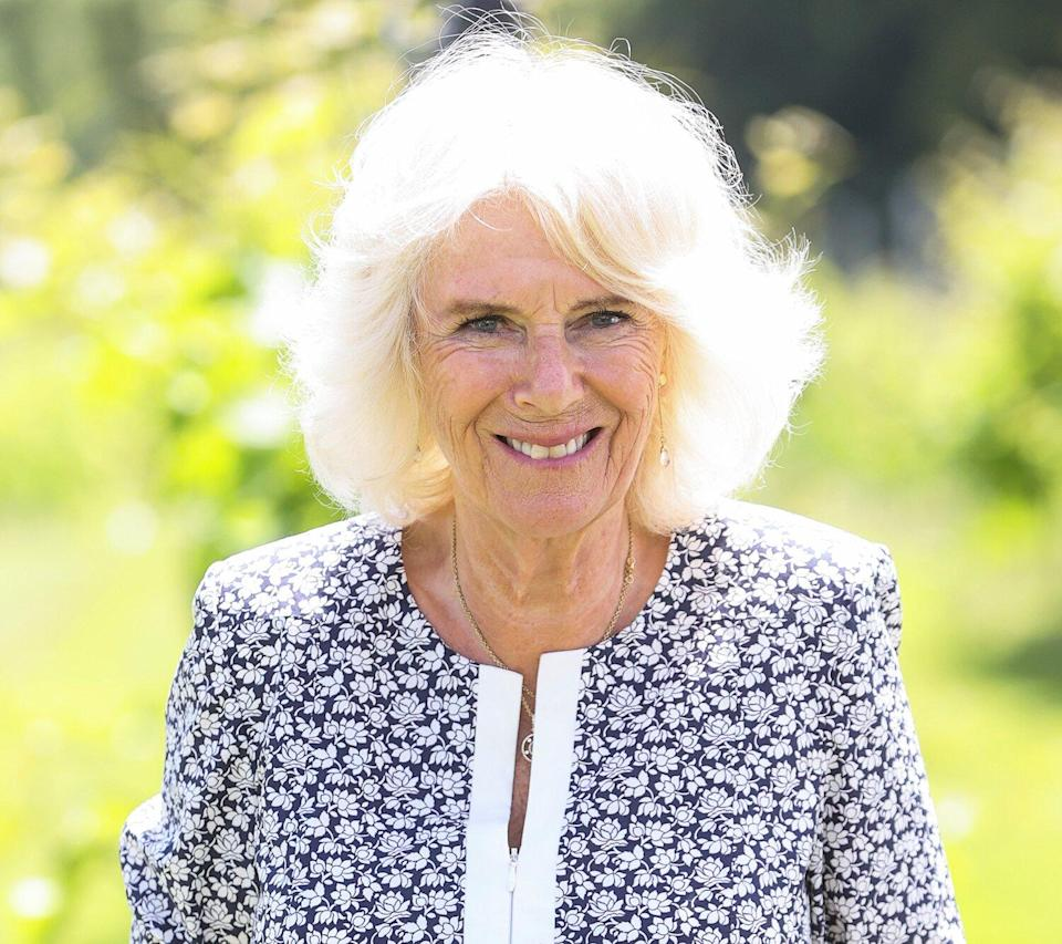 Camilla, Duchess of Cornwall holds a vine leaf during a visit to Llanerch Vineyard on July 07, 2021 in Pontyclun, Wales.