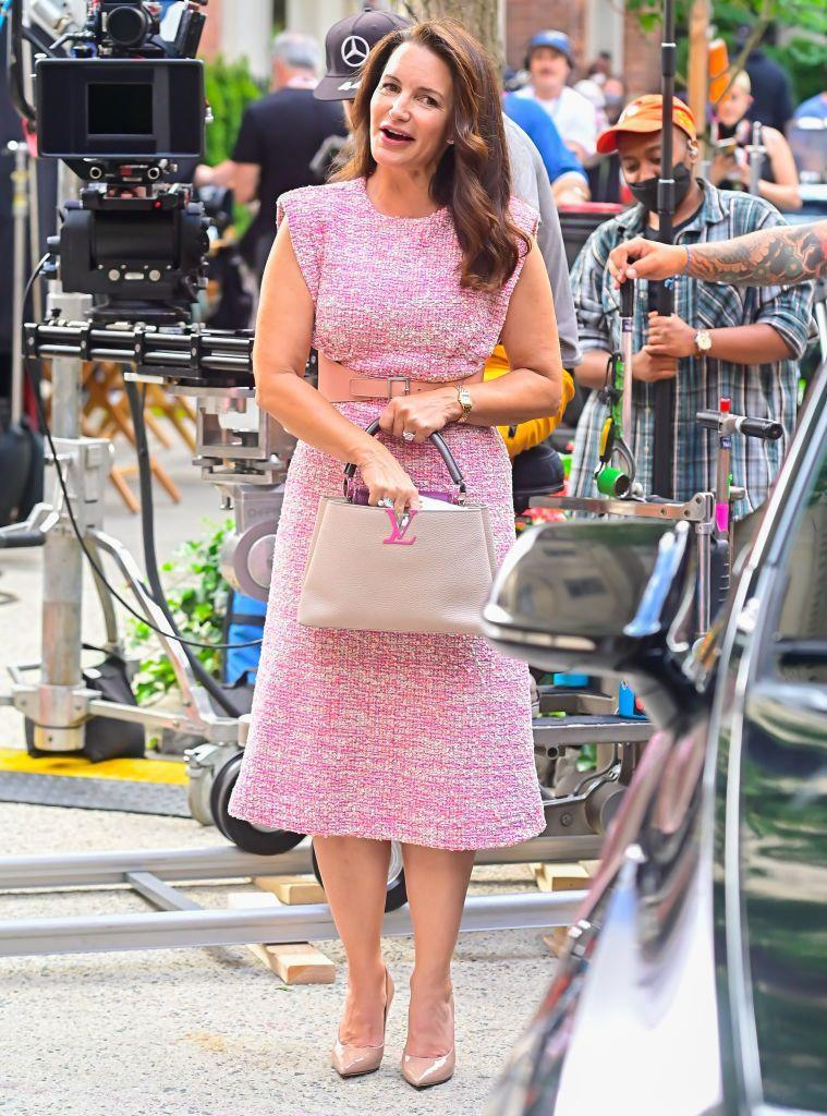 """<p>Snapped filming pretty in pink was Kristin Davis, wearing a St John tweed midi dress (which retails for £1,5225) and nude pumps by Jimmy Choo. In typical Charlotte York-Goldenblatt style she wore a <a href=""""https://www.goldsmiths.co.uk/c/Brands/Cartier/Panthere-de-Cartier"""" rel=""""nofollow noopener"""" target=""""_blank"""" data-ylk=""""slk:Cartier panthere watch"""" class=""""link rapid-noclick-resp"""">Cartier panthere watch</a> on her wrist while carrying a Louis Vuitton Capucines bag.</p><p><a class=""""link rapid-noclick-resp"""" href=""""https://www.harrods.com/en-gb/shopping/st-john-tweed-midi-dress-16907988"""" rel=""""nofollow noopener"""" target=""""_blank"""" data-ylk=""""slk:SHOP NOW"""">SHOP NOW</a> St John Tweed Midi Dress</p><p><a class=""""link rapid-noclick-resp"""" href=""""https://www.farfetch.com/uk/shopping/women/jimmy-choo-love-100-pumps-item-14214206.aspx"""" rel=""""nofollow noopener"""" target=""""_blank"""" data-ylk=""""slk:SHOP NOW"""">SHOP NOW</a> Jimmy Choo Love 100 Pumps, £525</p><p><a class=""""link rapid-noclick-resp"""" href=""""https://us.vestiairecollective.com/women-bags/louis-vuitton/capucines/"""" rel=""""nofollow noopener"""" target=""""_blank"""" data-ylk=""""slk:SHOP NOW"""">SHOP NOW</a> Louis Vuitton capucines bags on Vestiaire</p>"""