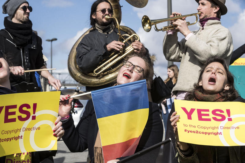 FILE - In this Tuesday March 26, 2019 file photo, people gather at the front of the European Parliament building in Strasbourg, France, to show their support for the copyright bill. The European Union approved on Monday April 15, 2019, a copyright law that aims to give more protection to artists and news organizations but which critics say will stifle freedom of speech and online creativity and punish smaller web companies. (AP Photo/Jean-Francois Badias, File)