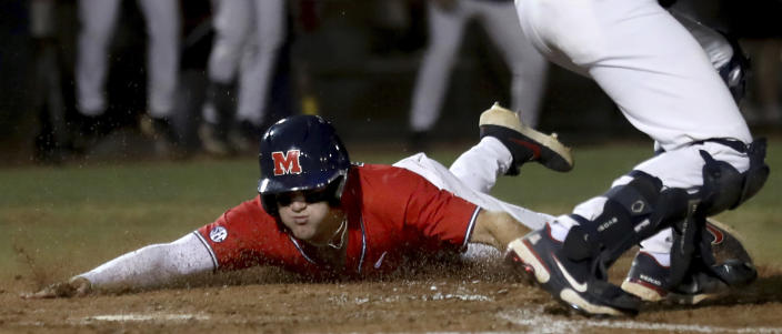 Mississippi's John Rhys Plumlee (10) skids across the plate with the second run on a two-run hit by Jacob Gonzalez during the second inning of an NCAA college baseball tournament super regional game Saturday, June 12, 2021, in Tucson, Ariz. (Kelly Presnell/Arizona Daily Star via AP)