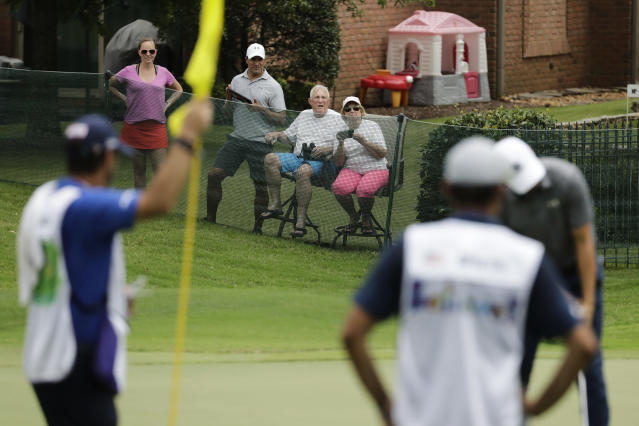 Residences watch from a private home near the17th green during the first round of the World Golf Championship-FedEx St. Jude Invitational Thursday, July 30, 2020, in Memphis, Tenn. (AP Photo/Mark Humphrey)