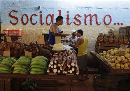 Vendors wait for customers at their stalls, with prices tagged in Cuban pesos, at a market in Havana