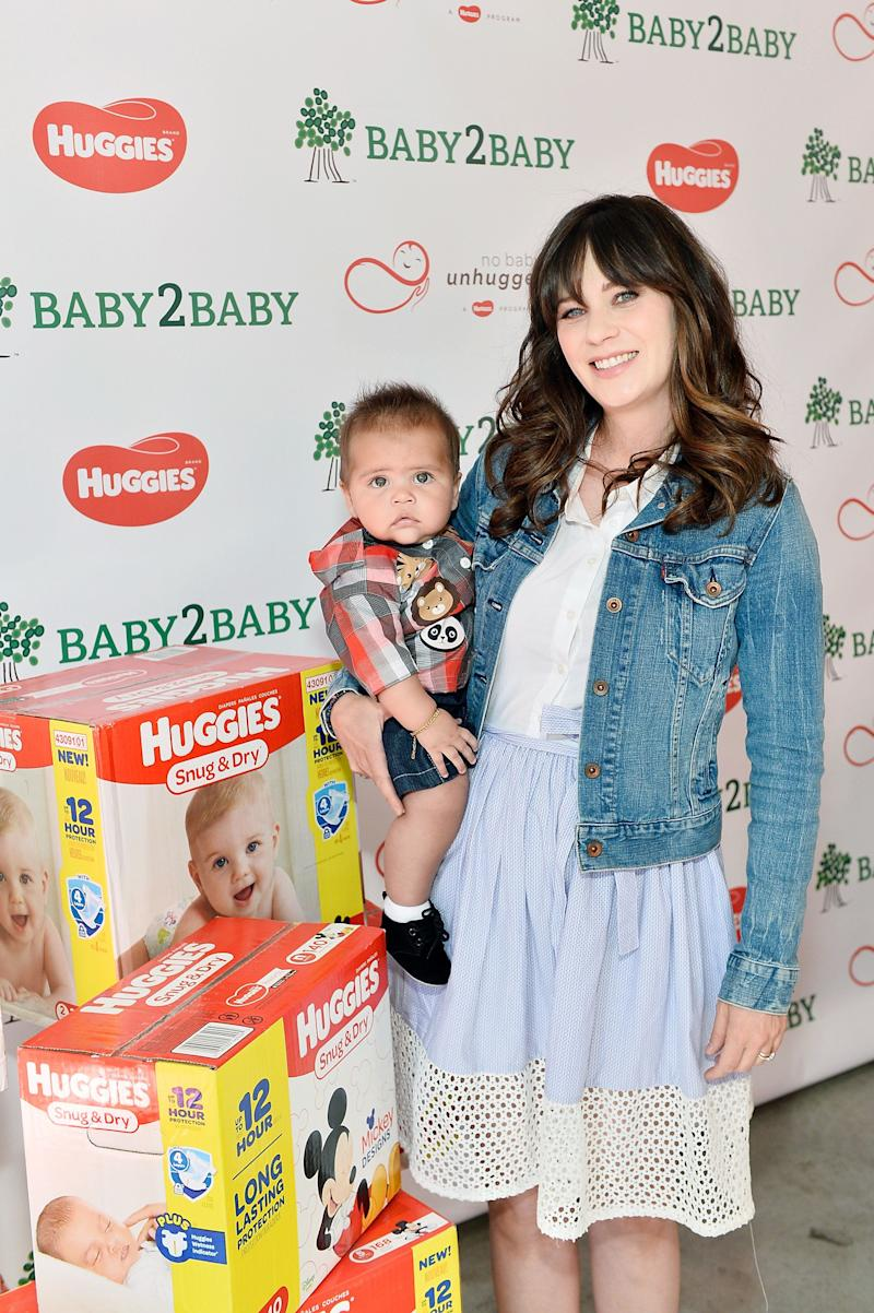 """""""You shouldn't have to choose between diapers and food or diapers and clothes. It should be something that's a given,"""" Deschanel told HuffPost after her event. For the photo above, she posed witha child who is part of the Baby2Baby community."""