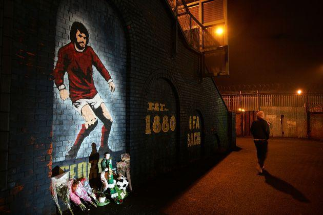 BELFAST, UNITED KINGDOM - DECEMBER 2:  Floral tributes create a shrine in front of a mural for late soccer hero George Best at the entrance to Windsor Park football ground in Belfast on December 2, 2005, Belfast Northern Ireland. Legendary footballer George Best died on November 11 after several weeks of ill health at the age of 59. He will buried tomorrow with up to half a million people expected to attend his funeral.  (Photo by Christopher Furlong/Getty Images) (Photo: Christopher Furlong via Getty Images)