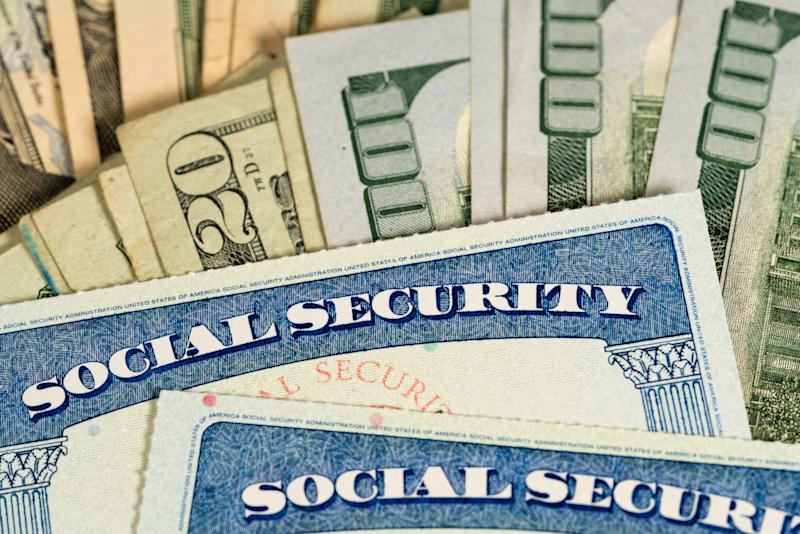 Two Social Security cards lying atop fanned piles of cash bills.