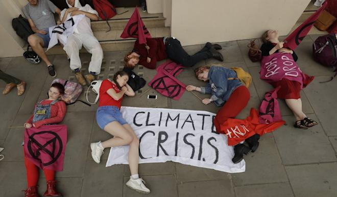 Extinction Rebellion climate change protesters stage a die-in outside the Royal Opera House in London to demand that they drop oil producer BP as a sponsor. Photo: AP