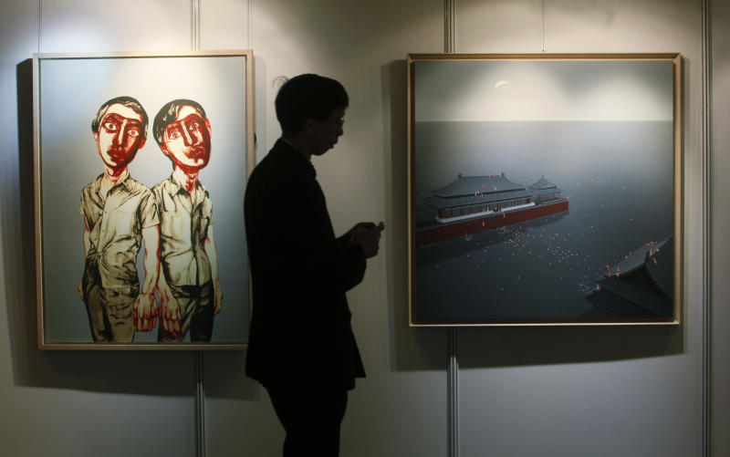"A man walks past paintings titled ""Flooding the Forbidden City No.10"", right, by Chinese artist Chen Lianqing and ""Two Men (from Mask Series)"" by Chinese artist Zeng Fanzhi at the Seoul Auction in Hong Kong Tuesday, April 3, 2012. Auctioneers in Hong Kong have sold 10 paintings seized from a South Korean bank that collapsed last year amid a corruption scandal to raise $2.4 million to help repay depositors. The paintings included works by noted Chinese artists Zeng and Zhang Xiaogang and American Julian Schnabel. (AP Photo/Kin Cheung)"