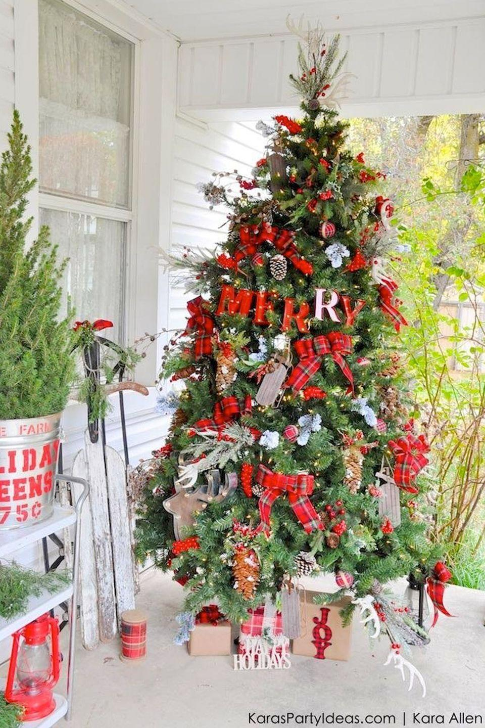 """<p>Plaid ribbon bows add playful pops color to this vibrant tree. </p><p><em><strong>G</strong><strong>et the tutorial at <a href=""""http://karaspartyideas.com/2015/10/rustic-farm-house-cabin-christmas-tree-michaels-dream-tree-challenge-2015.html"""" rel=""""nofollow noopener"""" target=""""_blank"""" data-ylk=""""slk:Kara's Party Ideas"""" class=""""link rapid-noclick-resp"""">Kara's Party Ideas</a>. </strong></em></p><p><a class=""""link rapid-noclick-resp"""" href=""""https://www.amazon.com/Natural-Decorative-Winter-Holiday-Filler/dp/B075Q98P4D/?tag=syn-yahoo-20&ascsubtag=%5Bartid%7C10070.g.2025%5Bsrc%7Cyahoo-us"""" rel=""""nofollow noopener"""" target=""""_blank"""" data-ylk=""""slk:BUY ARTIFICIAL PINE CONES"""">BUY ARTIFICIAL PINE CONES</a> </p>"""