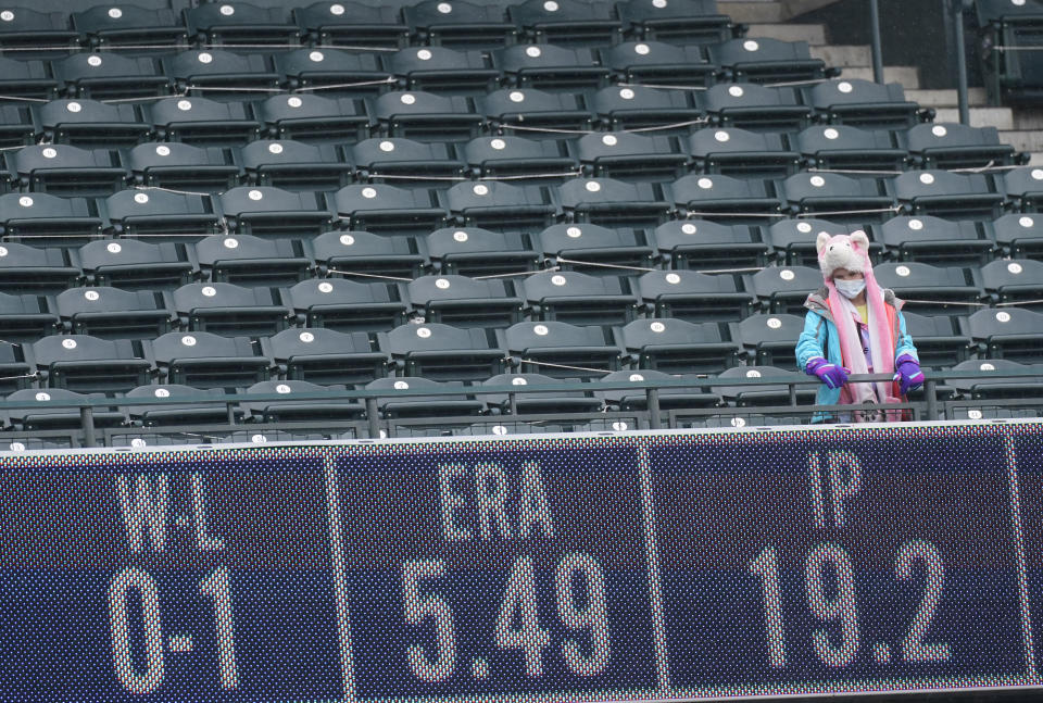 A lone fan looks on from the club level of Coors Field in the fourth inning of a baseball game between the Houston Astros and Colorado Rockies Wednesday, April 21, 2021, in Denver. (AP Photo/David Zalubowski)