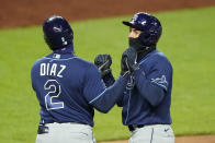Tampa Bay Rays' Willy Adames, right, and Yandy Diaz (2) celebrate after Adames scored on a single by Kevin Kiermaier during the fifth inning of a baseball game against the Kansas City Royals, Monday, April 19, 2021, in Kansas City, Mo. (AP Photo/Charlie Riedel)