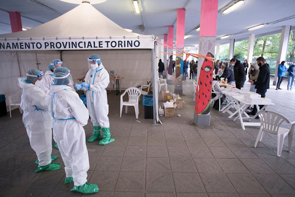 TURIN, ITALY - OCTOBER 16: General view of Medical staff in full PPE attends using swabs test on man in hotspot for swabs test for Covid-19 in Via Negarville  on October 16, 2020 in Turin, Italy. A new hotspot for swab tests for the prevention of Covid-19 for people returning to Italy and for schools is held at the covered market area of Via Negarville in Turin. Italy has also responded to the crowds and queues that have occurred in recent days for those who needed to swab test. (Photo by Stefano Guidi/Getty Images) (Photo: Stefano Guidi via Getty Images)