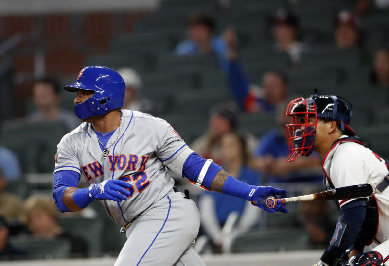 New York Mets Yoenis Cespedes drives in the go-ahead run with a single in front of Atlanta Braves catcher Kurt Suzuki during the 12th inning of a baseball game Friday