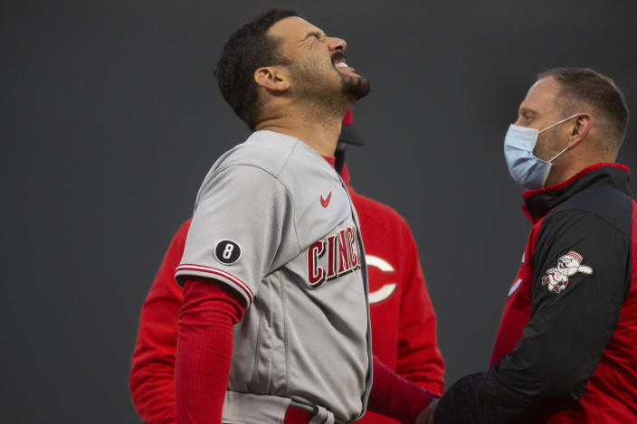 Cincinnati Reds' Eugenio Suárez, left, reacts as a trainer examines the hand on which he was hit by a pitch during the fourth inning of a baseball game against the San Francisco Giants, Monday, April 12, 2021, in San Francisco, Calif. (AP Photo/D. Ross Cameron)