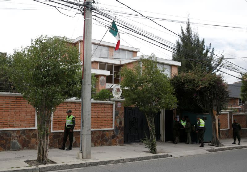 Police officers stand guard next to Mexico's embassy in La Paz