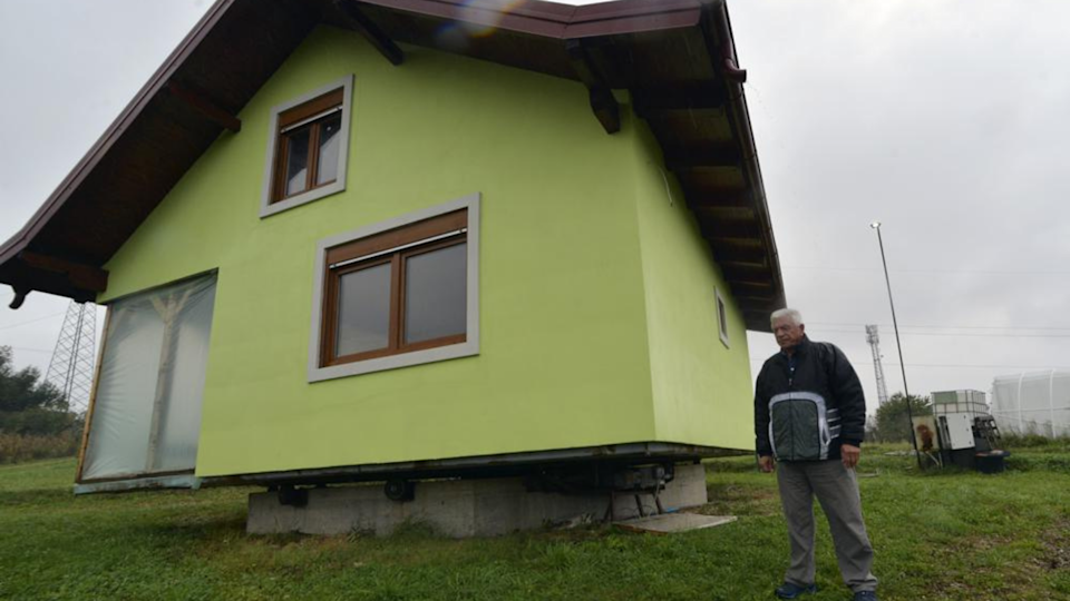 Bosnian man Vojin Kusic stands next to the rotating house he built for his wife in northern Bosnia.