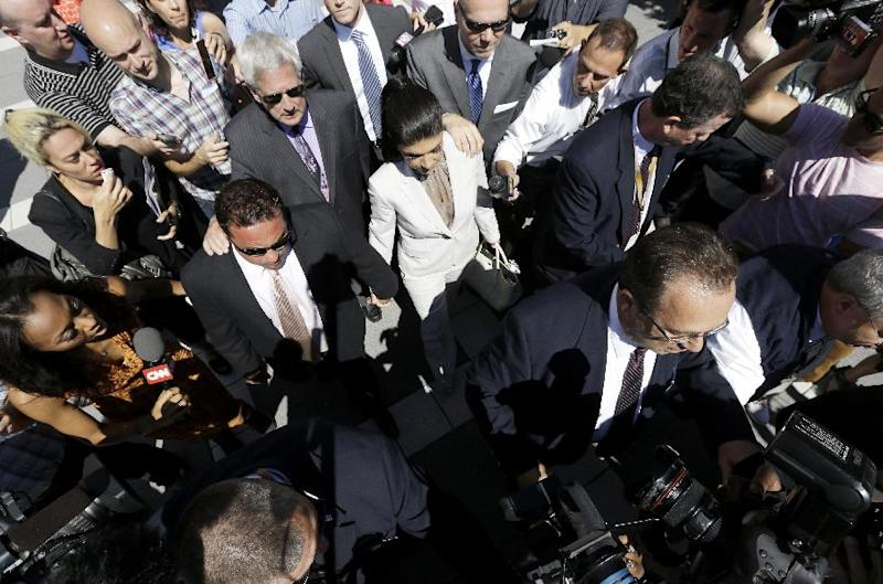 """Members of the press swarm Giuseppe """"Joe"""" Giudice, 43, center left, and his wife Teresa Giudice, 41, center, of Montville Township, N.J., as they walk out of Martin Luther King, Jr. Courthouse after a court appearance, Tuesday, July 30, 2013, in Newark, N.J. The two stars of the """"Real Housewives of New Jersey"""" are charged in a 39-count indictment with conspiracy to commit mail and wire fraud, bank fraud, making false statements on loan applications and bankruptcy fraud. Joe Giudice also failed to file tax returns for the years 2004 through 2008, when he is alleged to have earned nearly $1 million, the government said. . (AP Photo/Julio Cortez)"""