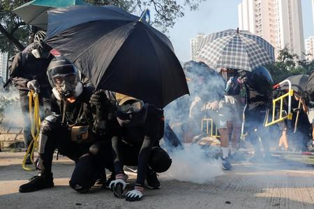 Anti-government protesters protect themselves with umbrellas among tear gas during a demonstration on China's National Day, in Wong Tai Sin, Hong Kong