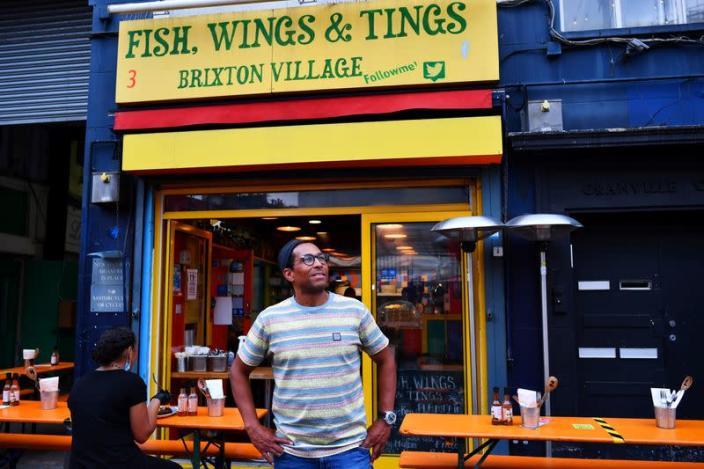 Brian Danclair, owner of Fish, Wings & Tings, stands outside his restaurant at Brixton Village in London