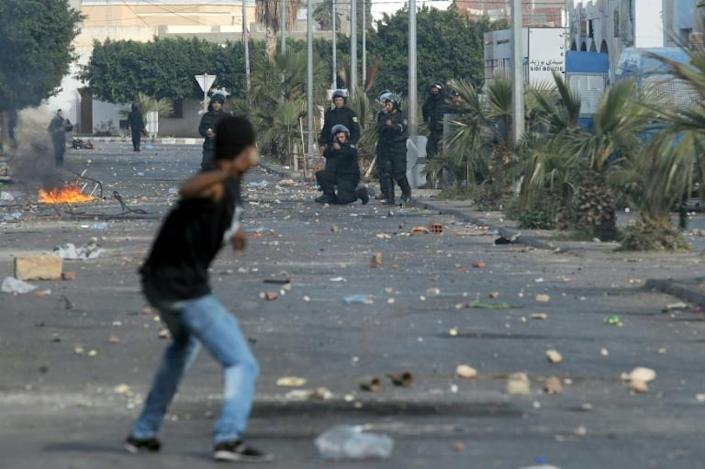 A member of the Tunisian security forces takes aim towards a demonstrator who prepares to throw a rock towards them during clashes in January 2011 near Sidi Bouzid (AFP Photo/STR)