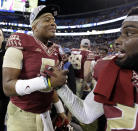 Florida State quarterback Jameis Winston (5) celebrates with a teammate after winning the Atlantic Coast Conference championship NCAA college football game in Charlotte, N.C., Saturday, Dec. 6, 2014. Florida State won 37-35. (AP Photo/Chuck Burton)