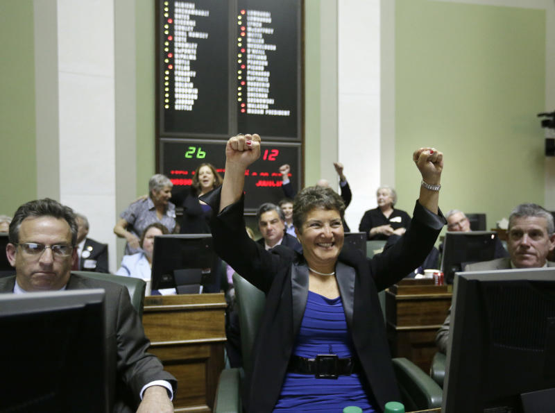Rhode Island state Sen. Donna Nesselbush, D-Pawtucket, center, reacts seconds after the state senate passed a same-sex marriage bill at the Statehouse, in Providence, R.I., Wednesday, April 24, 2013. Nesselbush was the main sponsor of the bill. (AP Photo/Steven Senne)