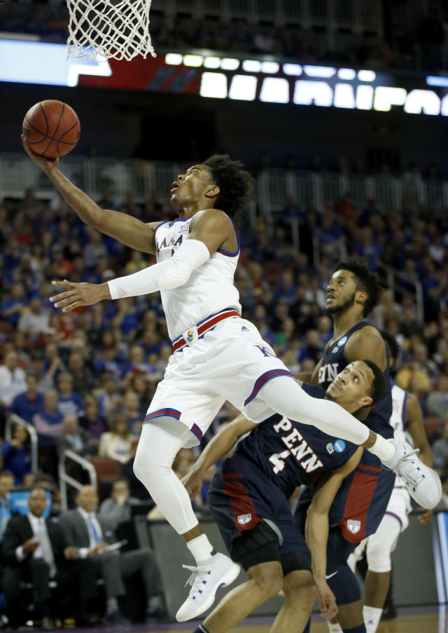 Kansas guard Devonte' Graham gets past Pennsylvania guard Darnell Foreman (4) to put up a shot during the second half of an NCAA college basketball tournament first-round game, Thursday, March 15, 2018, in Wichita, Kan. Kansas won 76-60. (AP Photo/Charlie Riedel)