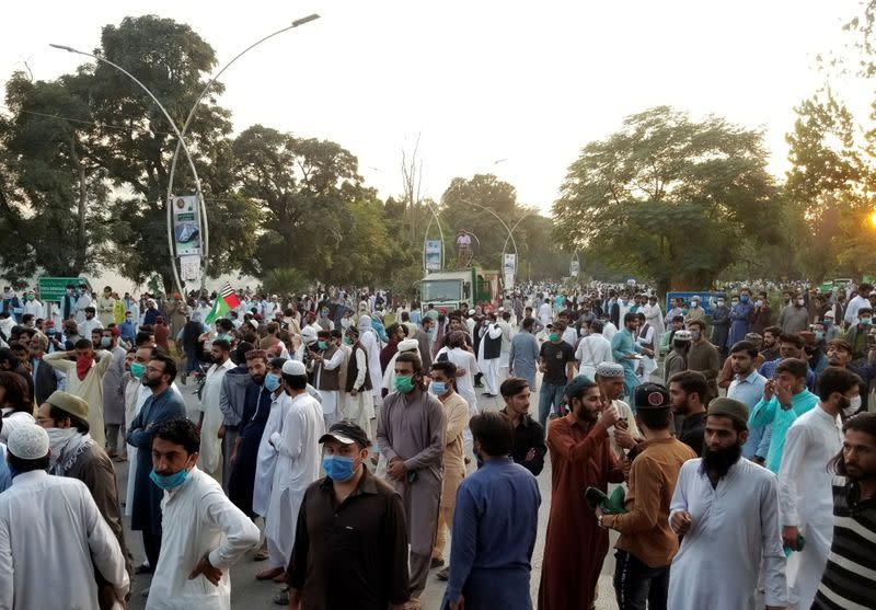 People gather to protest against the cartoon publications of Prophet Mohammad in France and French President Emmanuel Macron's comments, in Islamabad