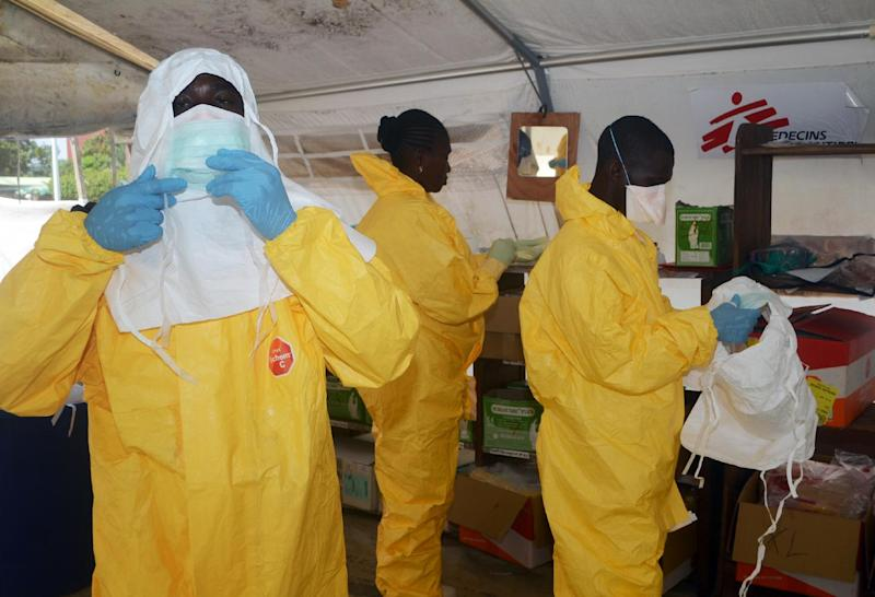 Members of Doctors Without Borders put on protective gear at the isolation ward of the Donka Hospital in Conakry, where people infected with the Ebola virus are being treated, June 28, 2014