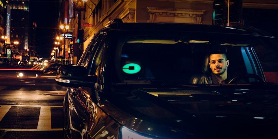A driver at night with an Uber beacon shining in his car.