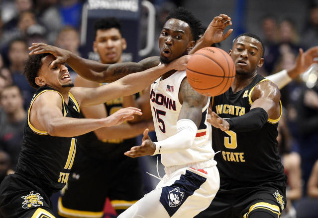 Connecticut's Sidney Wilson, center, fights for the ball between Wichita State's Noah Fernandes, left, and Trey Wade, right, in the first half of an NCAA college basketball game, Sunday, Jan. 12, 2020, in Hartford, Conn. (AP Photo/Jessica Hill)