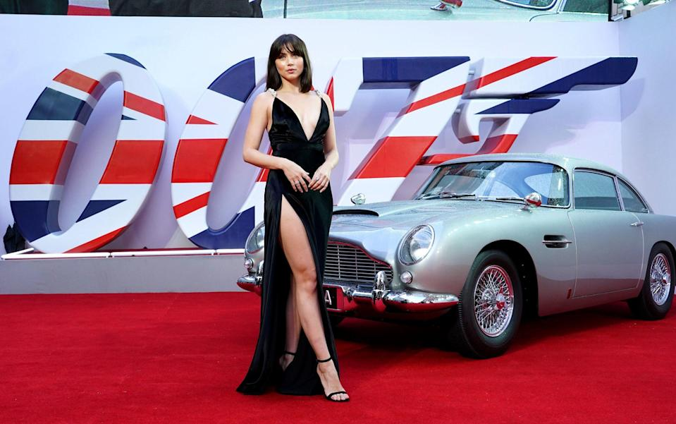Ana de Armas, who plays CIA agent Paloma, poses in front of James Bond's iconic Aston Martin