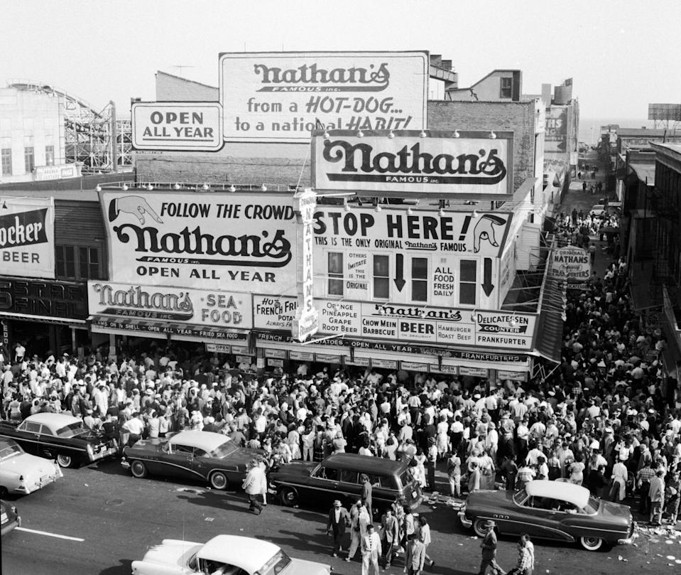 "Crowds gather outside the original Nathan's Famous hot dog stand on <a href=""https://www.cntraveler.com/activities/new-york/coney-island?mbid=synd_yahoo_rss"" rel=""nofollow noopener"" target=""_blank"" data-ylk=""slk:Coney Island"" class=""link rapid-noclick-resp"">Coney Island</a>. The stand was originally built in 1916 by Polish immigrant Nathan Handwerker with a $300 loan; today, the restaurant chain can be found all over the world."