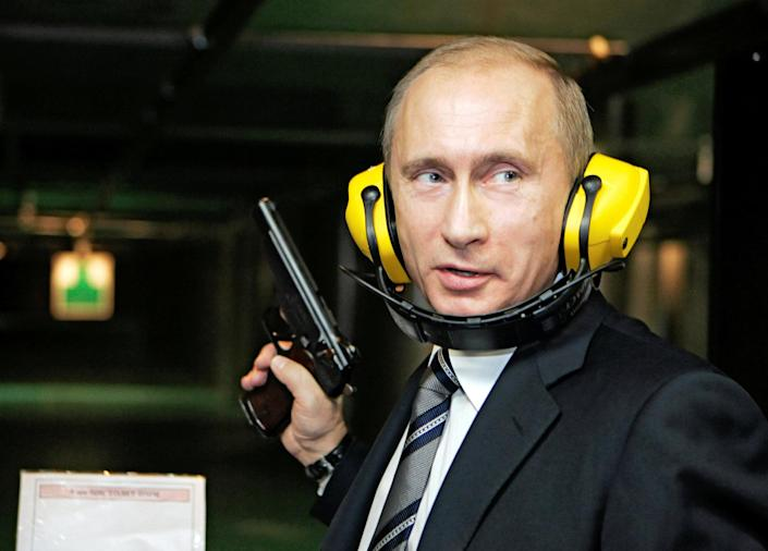 Russian President Vladimir Putin stands with a gun at a shooting gallery of the GRU military intelligence headquarters Reuters