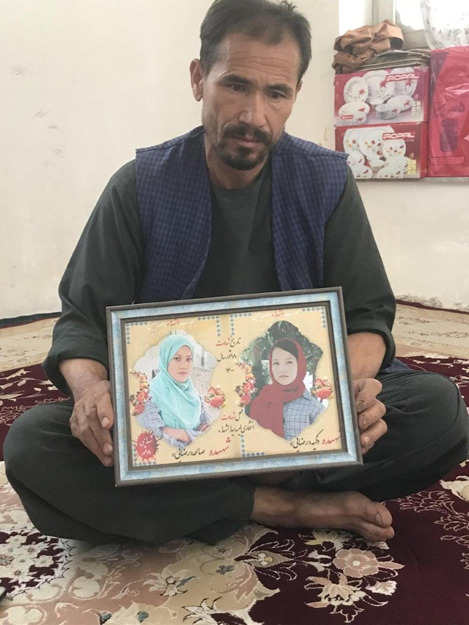 Rajab Ali Razayee holds a picture of his two daughters, who were killed in a school bombing in May (Kim Sengupta)