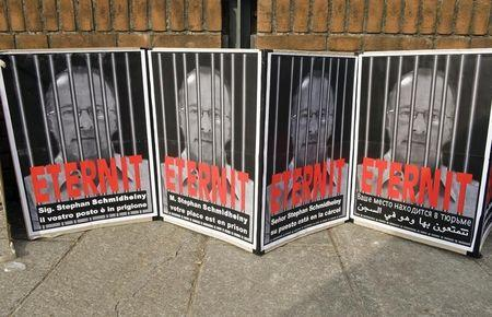 """Posters reading """"Stephan Schmidheiny your place is in prison"""" are displayed outside the courthouse during a trial against the Swiss firm Eternit's Italian plant in Turin"""