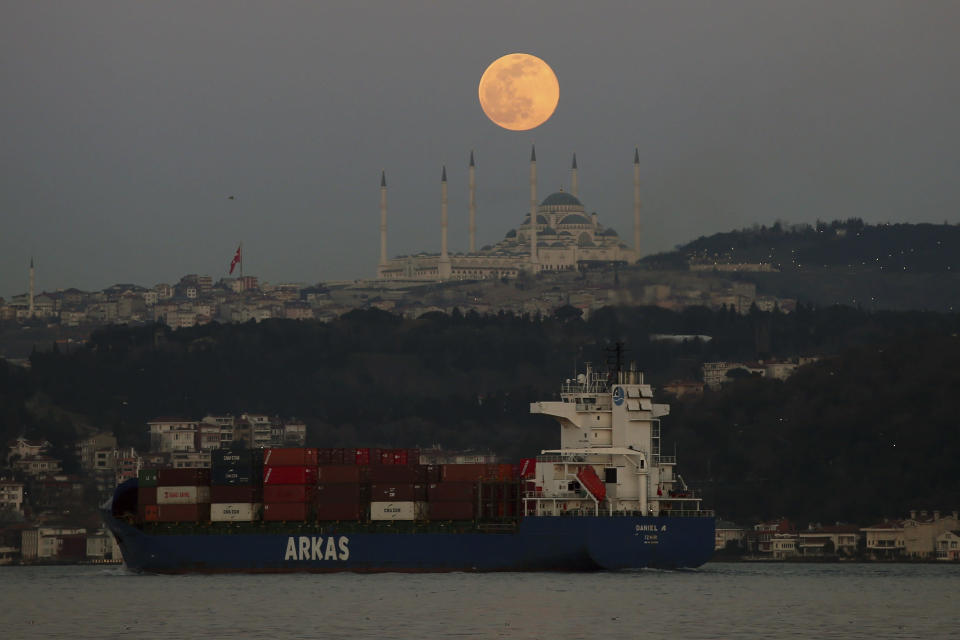 """The full moon rises over the sky in Istanbul, Sunday, March 28, 2021, with a view of the Camlica Mosque, the largest mosque in Asia Minor as a ship crosses the Bosphorus Strait separating European and Asian sides of the metropolis. The March full moon is called the """"Worm Moon"""". (AP Photo/Emrah Gurel)"""