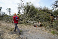 Logan Cunningham, of Canary Tree Service of Jacksonville, Fla., walks past tree debris as he waits for more equipment to arrive, in Lake Charles, La., in the aftermath of Hurricane Laura, Sunday, Aug. 30, 2020. (AP Photo/Gerald Herbert)