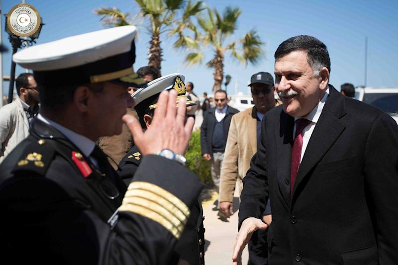 Libya's UN-backed Prime Minister-designate, Fayez al-Sarraj (R), is greeted by unidentified officials upon his arrival in Tripoli on March 30, 2016 (AFP Photo/)
